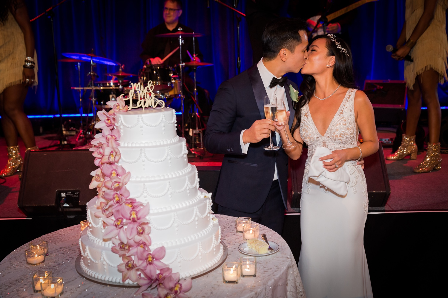 A newly wedded couple kissing next to their wedding cake during a wedding reception at Cipriani Wall Street in New York City.