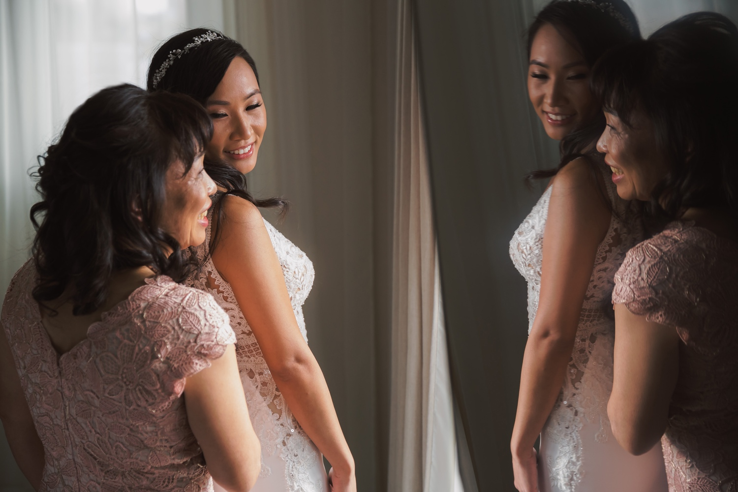 A portrait of a bride and her mother getting ready for a wedding ceremony at Cipriani Wall Street in New York City. Wedding Dress by Pronovias.