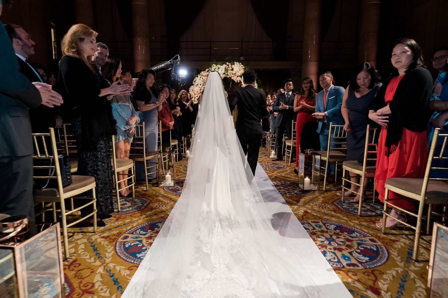 A bride and her father walking in an aisle during a wedding ceremony at Cipriani Wall Street in New York City. Wedding Dress by Pronovias