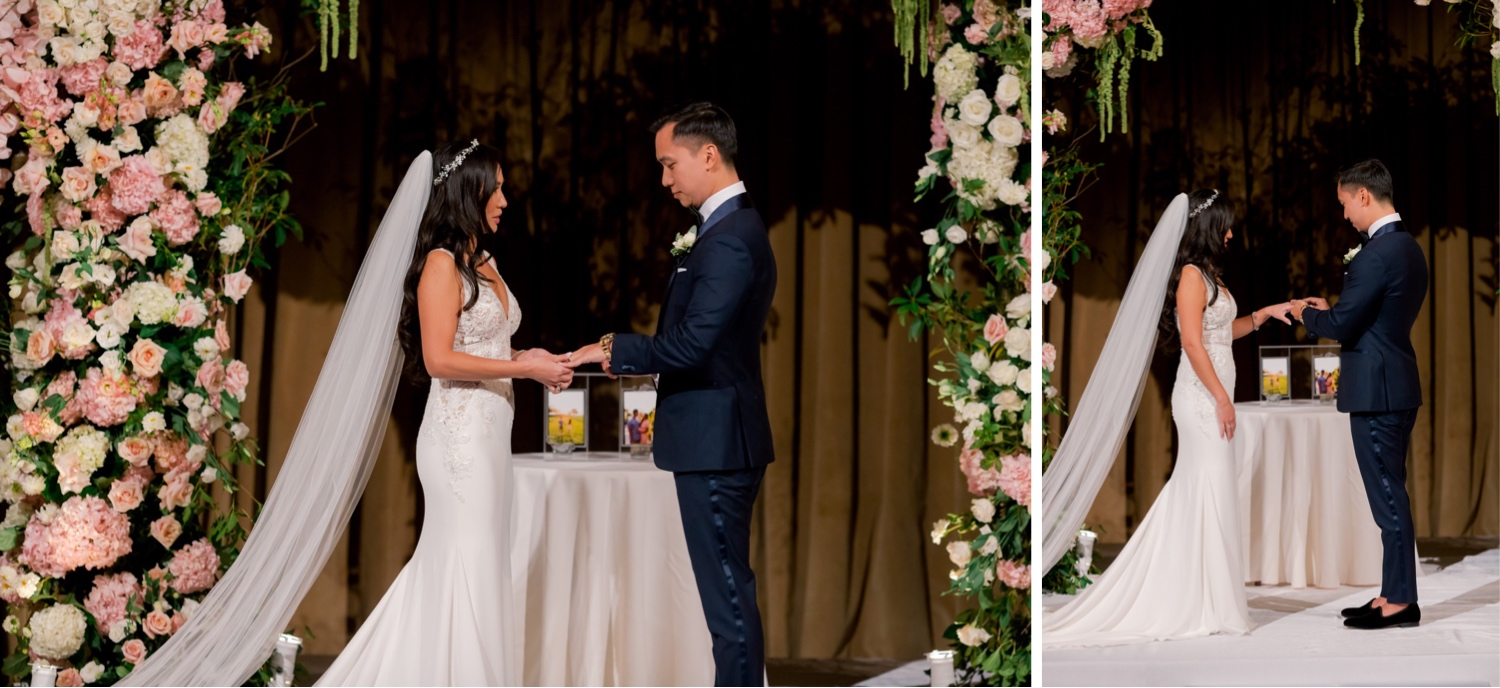 A bride and a groom exchanging their wedding rings during a wedding ceremony at Cipriani Wall Street in New York City. Wedding Dress by Pronovias