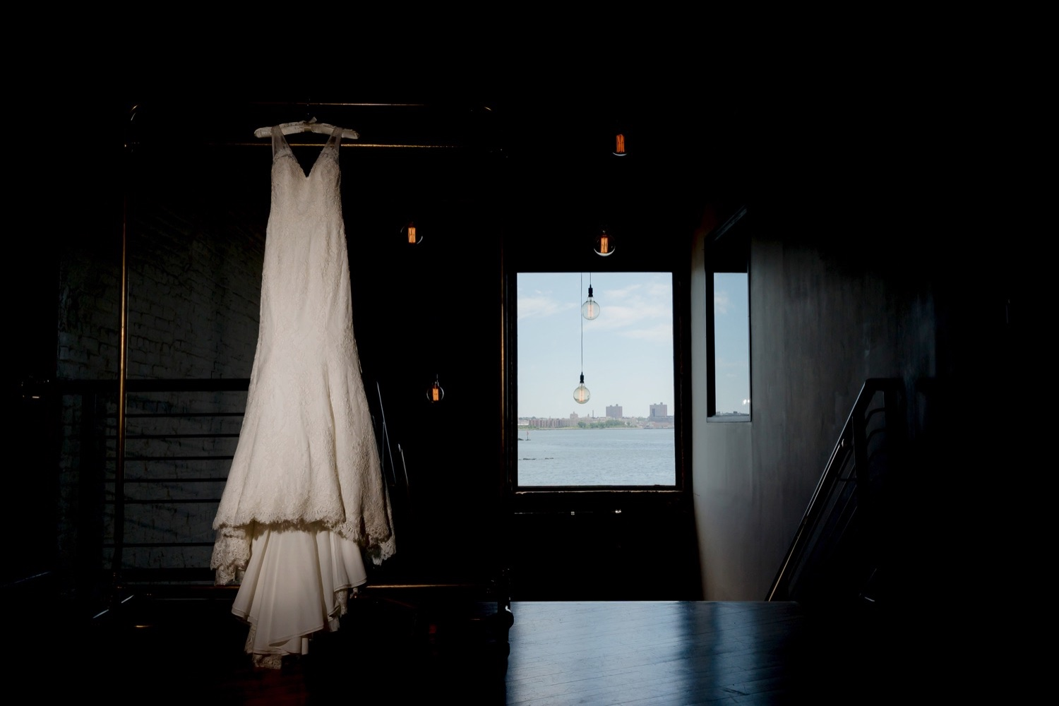 A bride's dress hanging inside a wedding venue at Liberty Warehouse in Brooklyn, New York.