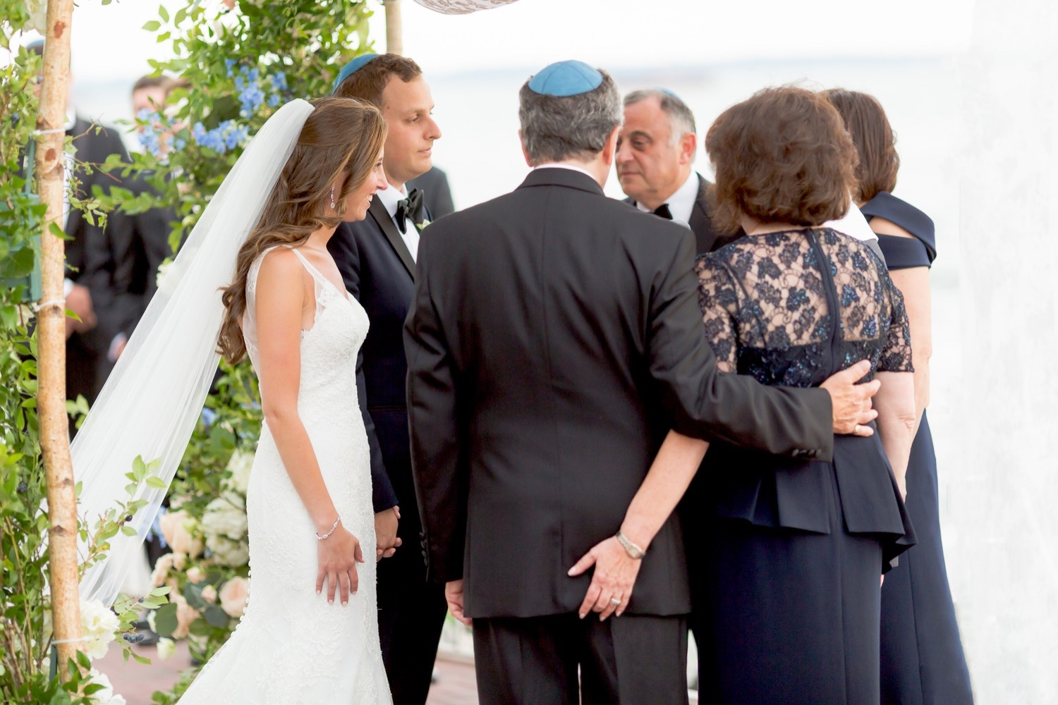 A bride, a groom and their parents gathered together around chuppah during a wedding ceremony at Liberty Warehouse, Brooklyn New York.