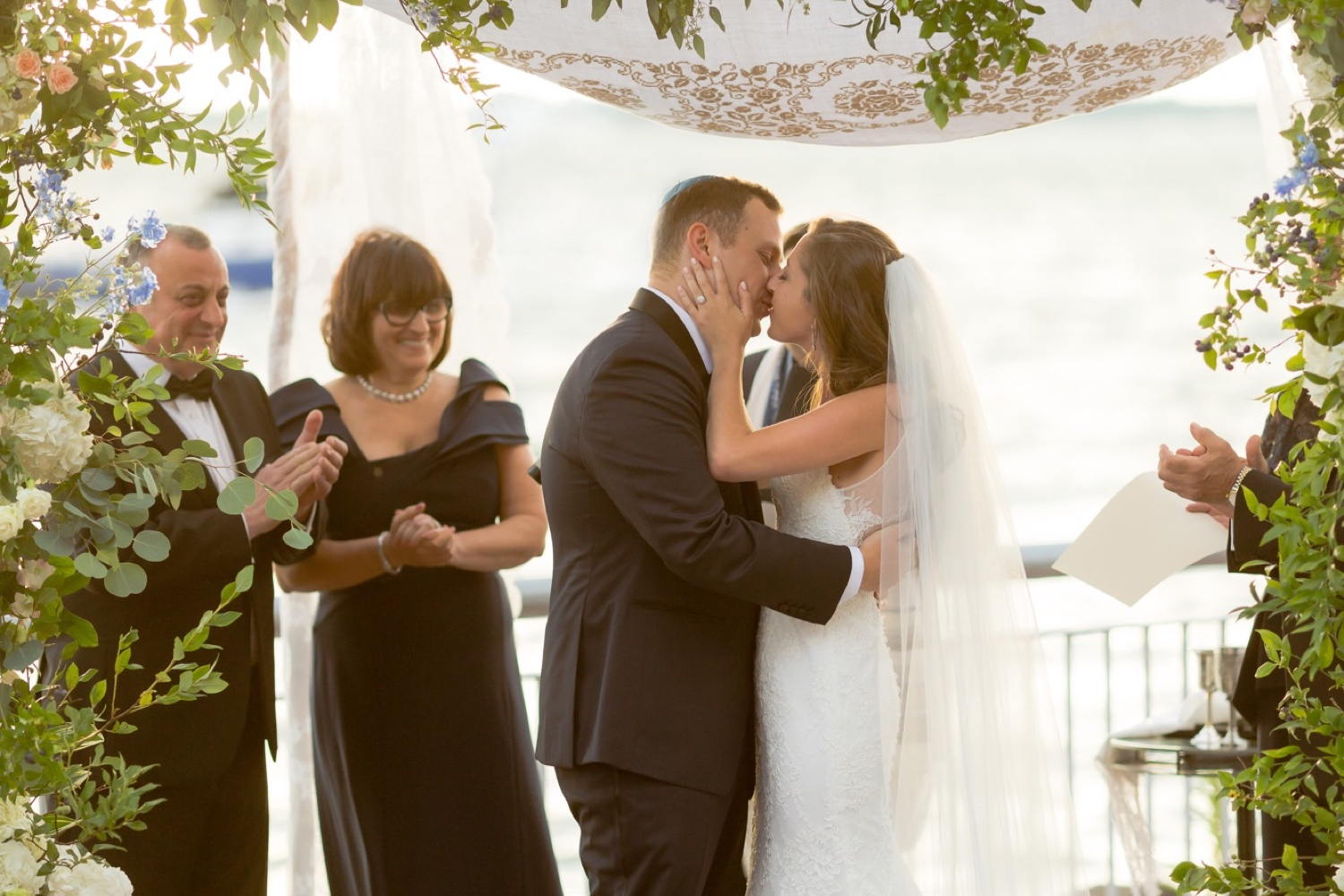 A first kiss as a husband and a wife during a jewish wedding ceremony at Liberty Warehouse, Brooklyn New York.