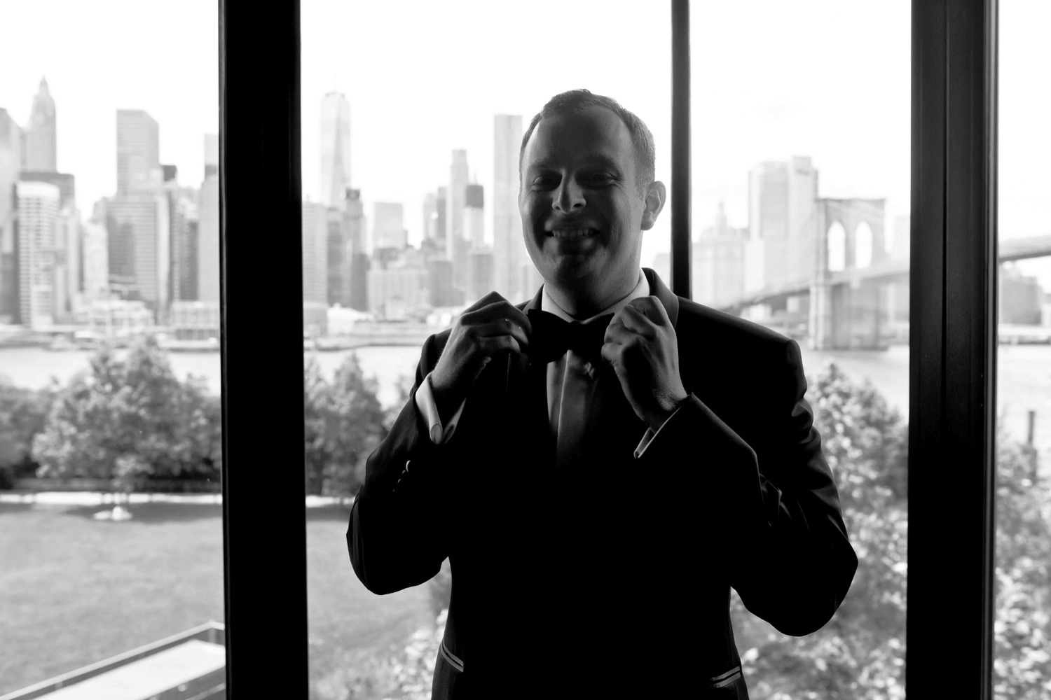A groom reshaping his bow tie on his wedding day at Liberty Warehouse in Brooklyn, New York.