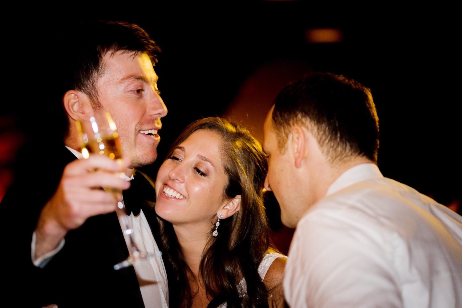 A newly wedded couple hugging a best man during a wedding reception at Liberty Warehouse, Brooklyn New York.