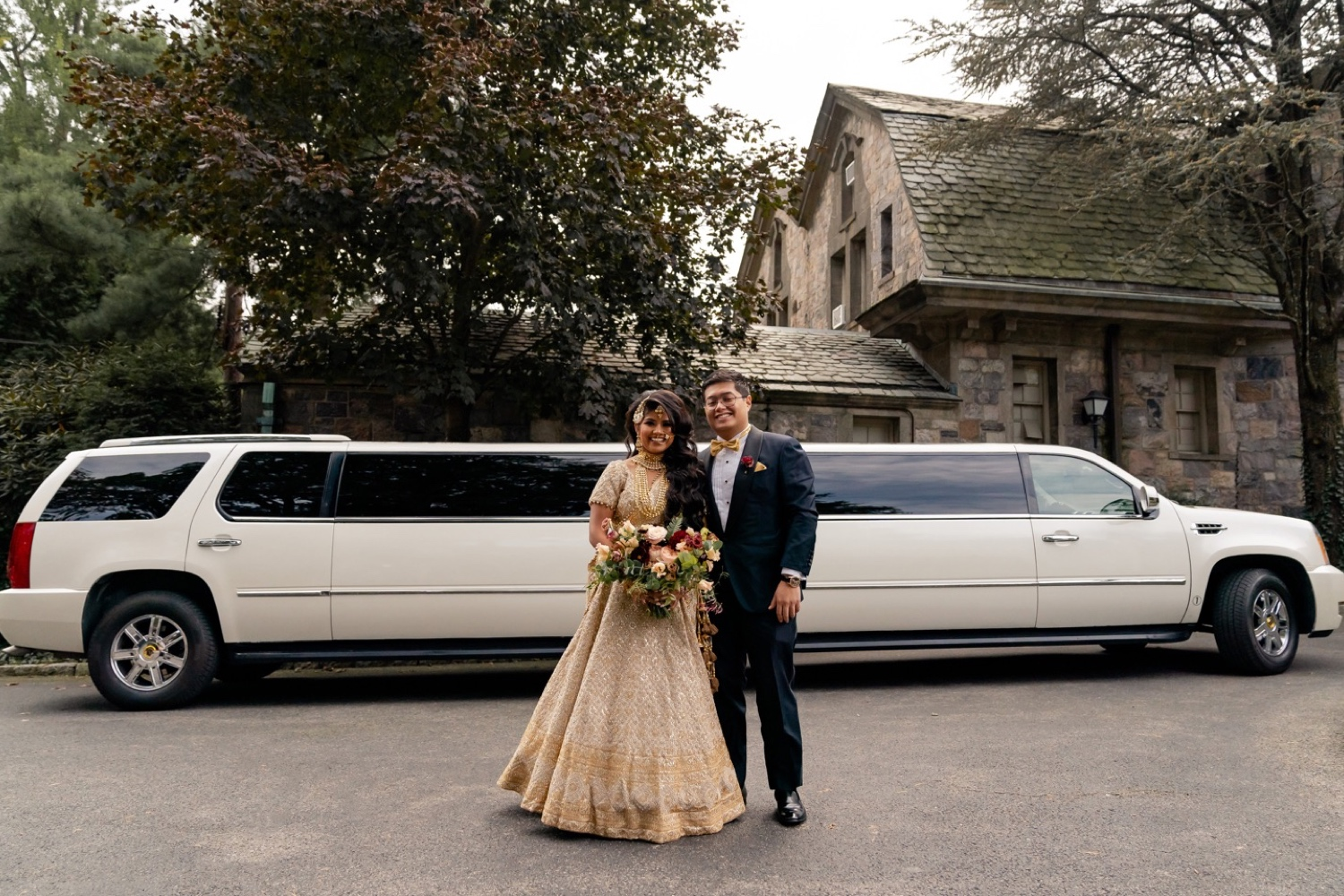 A groom and a bride posing for a picture in front of Tappan Hill Mansion.
