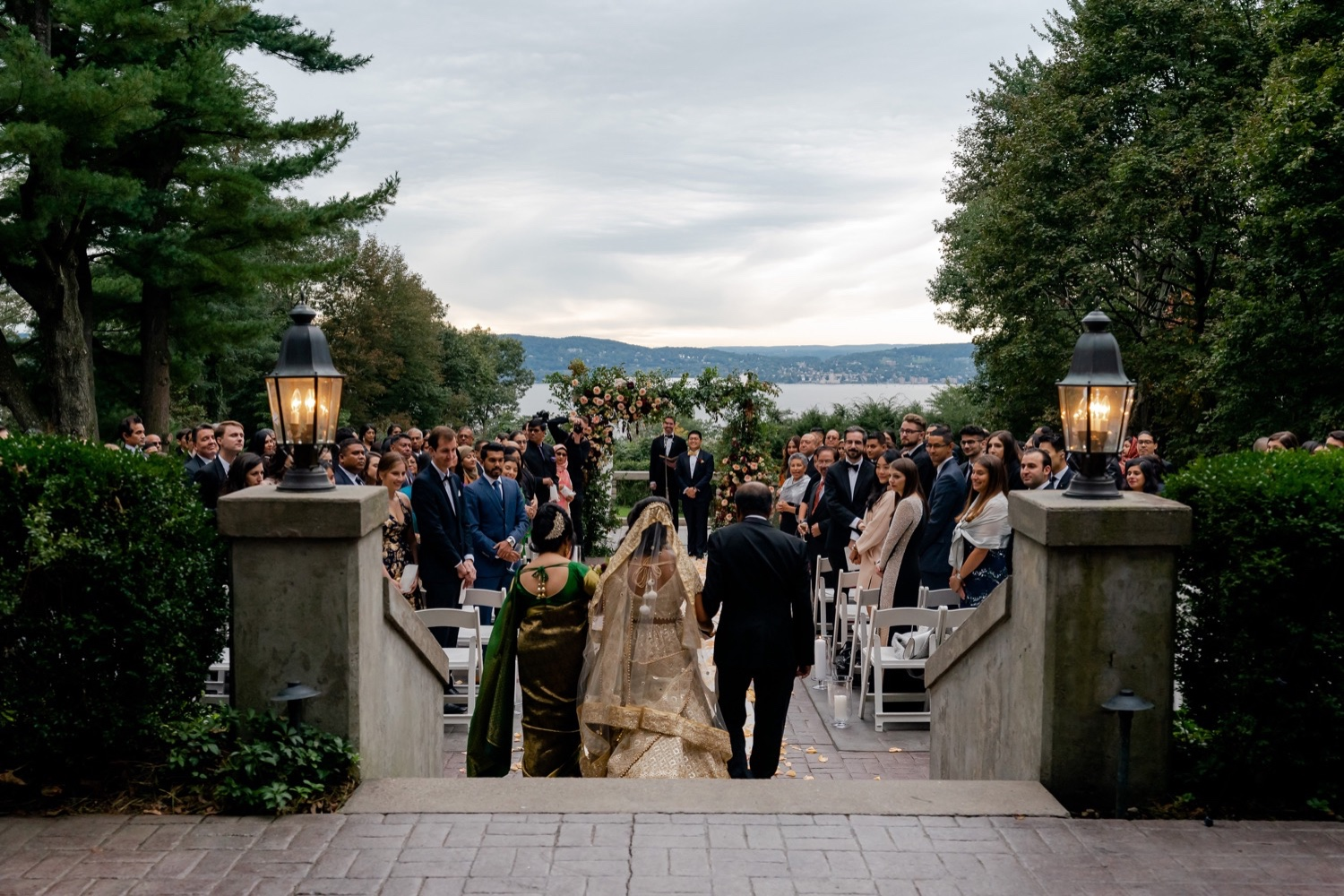 A groom and a whole wedding guests watching a bride coming into the wedding ceremony at the Tappan Hill Mansion.