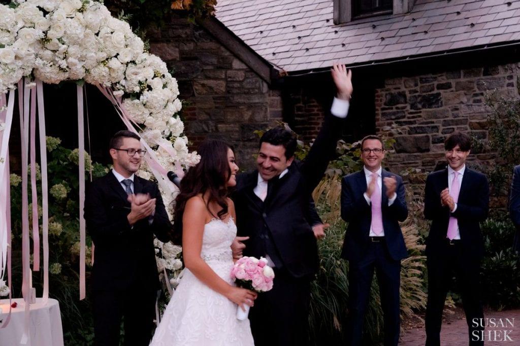 groom waving at blue hill stone barns